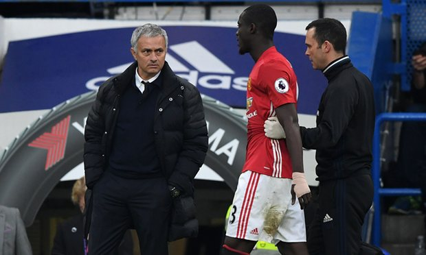 An injured Bailly is walked off the field by Manchester United medical staff.