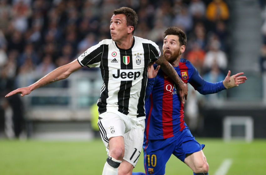 Former Juventus striker Mario Mandzukic engages in a tussle with Barcelona's Lionel Messi during a Champions League encounter.