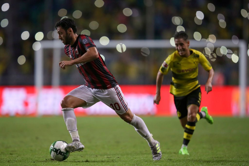 AC Milan midfielder Hakan Calhanoglu dribbles past a Dortmund player. (Getty Images)