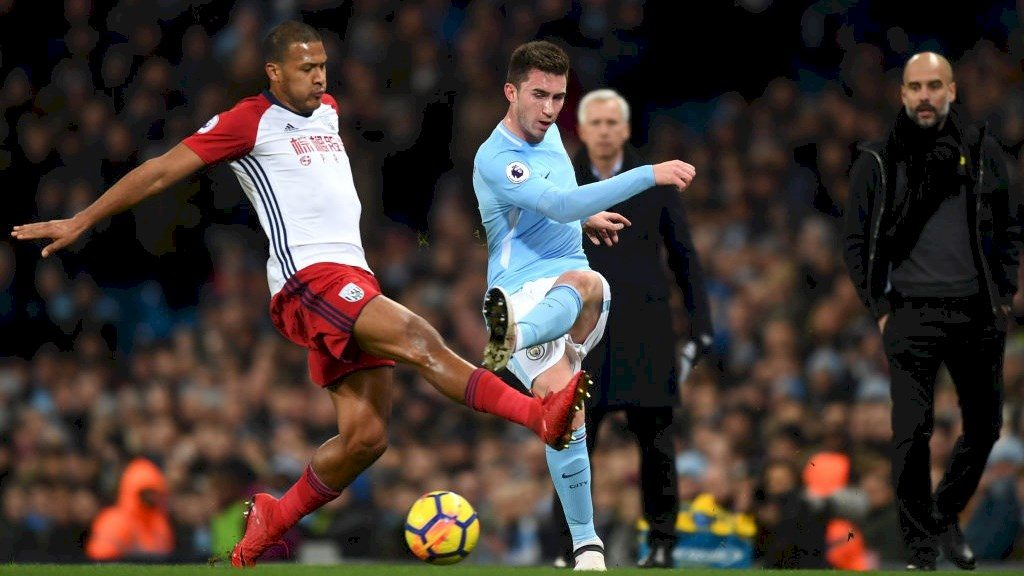 Guardiola watches on as City defender Laporte clears a ball during his side's league campaign early in the season.