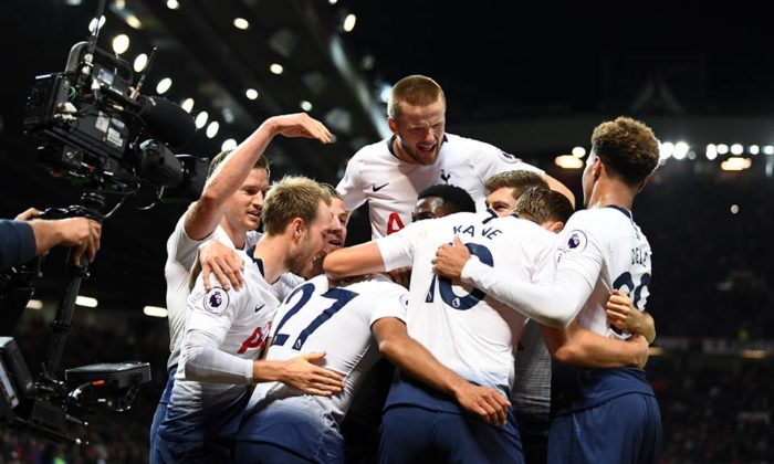 Tottenham players celebrate after scoring a goal during a Premier League game.