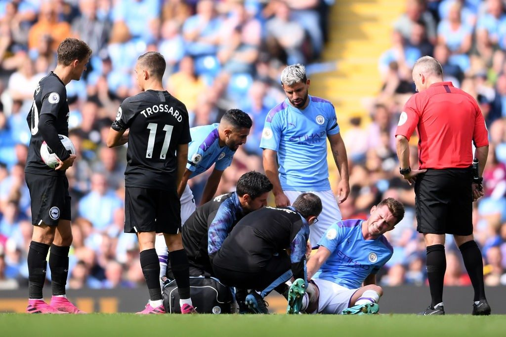 Sergio Aguero and Riyad Mahrez look on as an injured Aymeric Laporte sits in pain.