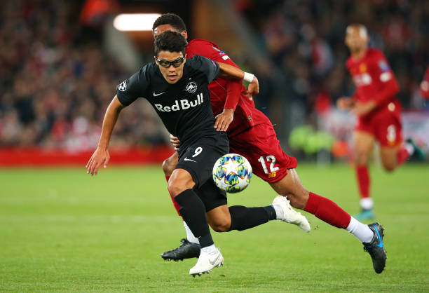 Hwang Hee-chan of Red Bull Salzburg holds off a challenge from Joe Gomez of Liverpool during the UEFA Champions League group E match between Liverpool FC and RB Salzburg at Anfield.