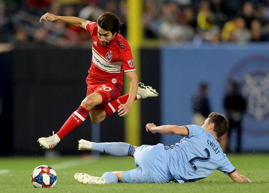 Nicolas Gaitan of Chicago Fire avoids the tackle by Ben Sweat of New York City FC at Yankee Stadium. (Getty Images)