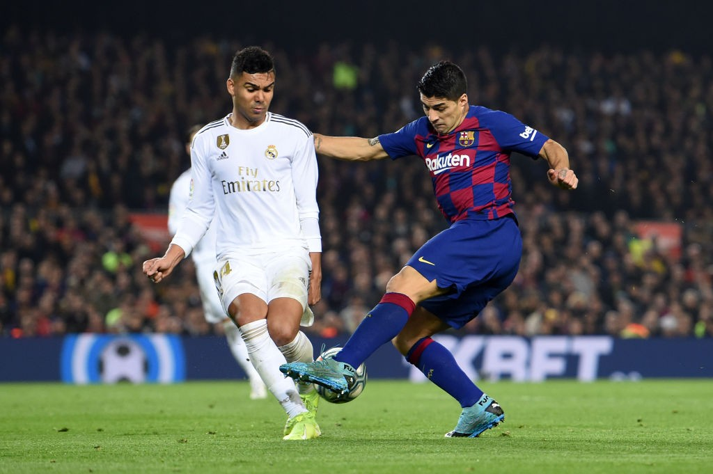 Casemiro engages in a tussle with Barcelona's Luis Suarez.