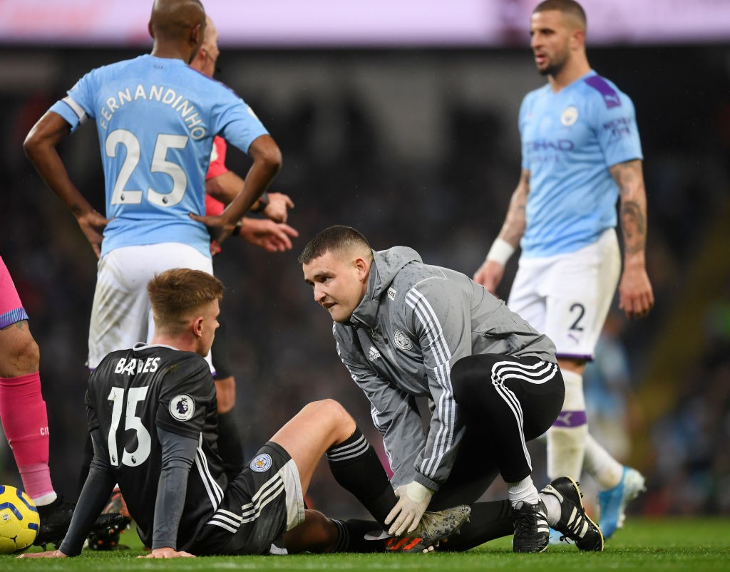 An injured Harvey Barnes talking to Leicester City medical staff.